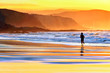 person running on beach at sunset