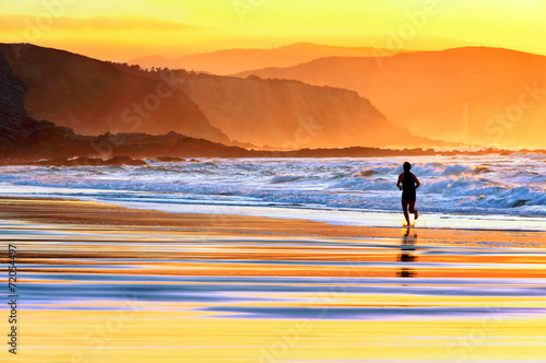 Foto Spatwand Zonsondergang op het Strand person running on beach at sunset