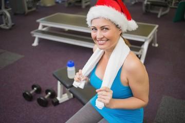Festive brunette smiling at camera in fitness studio