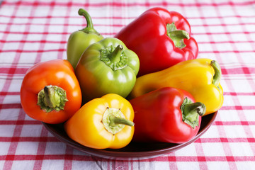 Pepper on plate on fabric background