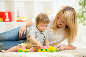 mom and kid boy playing block toys at home
