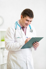 Portrait of smiling male doctor with clipboard at office