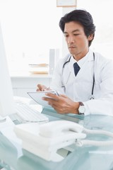 Focused doctor writing down notes