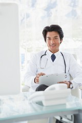 Smiling doctor reading over notes