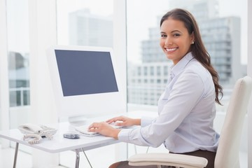 Smiling businesswoman working at her desk