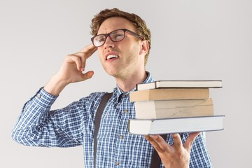 Geeky student holding a pile of books