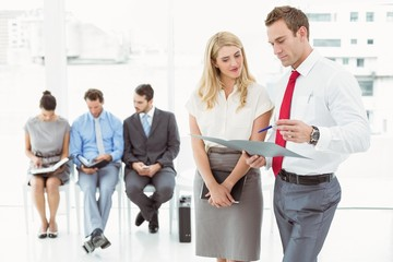 Businesspeople looking at file while people waiting
