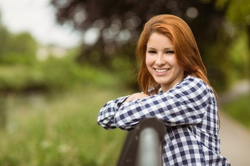 Gorgeous smiling redhead leaning against bridge