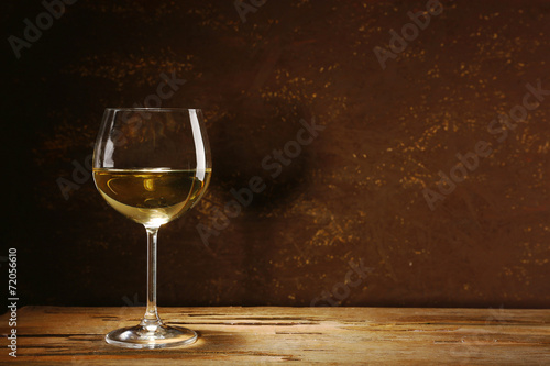 canvas print picture Goblet of white wine on wooden table on wooden wall background