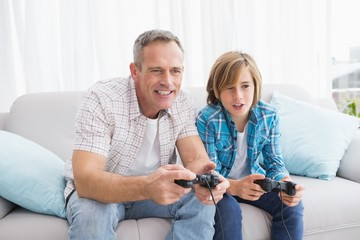 Son and father playing video games together on the couch