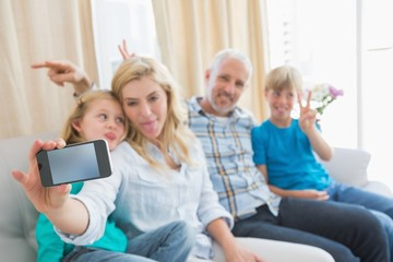 Happy family taking a selfie on couch