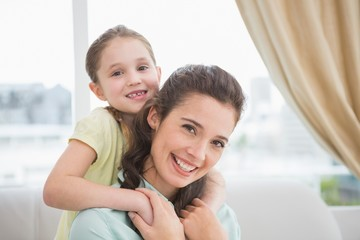 Cute mother and daughter smiling at camera