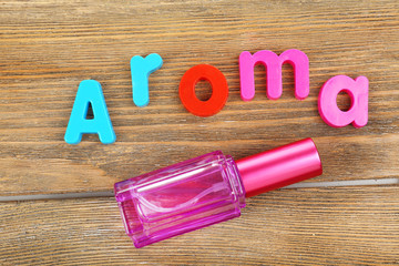 Aroma word formed with colorful letters on wooden background