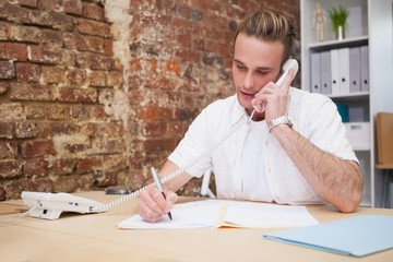 Man writing notes while on call