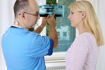 Dentist bei Gespräch mit Patient in Praxis
