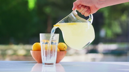 Fresh lemonade pouring into a glass outside