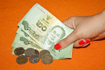 Thai baht - banknotes and coins in woman's hand