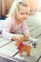 Little girl playing with Christmas decorations - reindeer and co