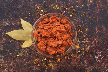 Curry paste in glass bowl with various spices