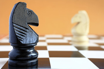 Chessmen black and white knight on a chessboard.