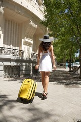 woman back walking with yellow suitcase
