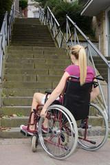 Frau mit Behinderung vor Hindernis im Rollstuhl