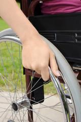 Hand an Rad-Reifen von Rollstuhl