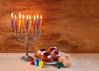 jewish holiday Hanukkah with menorah, doughnuts and wooden dreid
