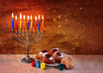 jewish holiday Hanukkah with menorah, doughnuts and wooden dreid