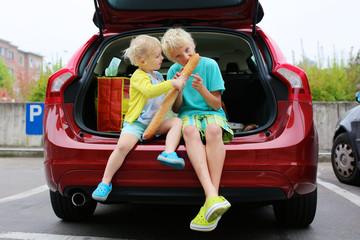 Brother and sister sitting in trunk of the car eating bread