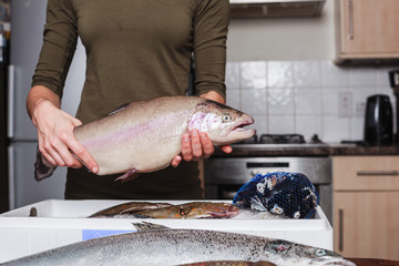 Young woman holding a trout in her kitchen