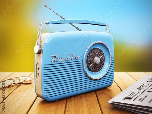 Leinwanddruck Bild Old radio on wooden table outdoors