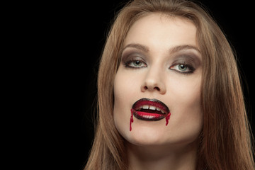 Close-up portrait of a smiling gothic vampire woman