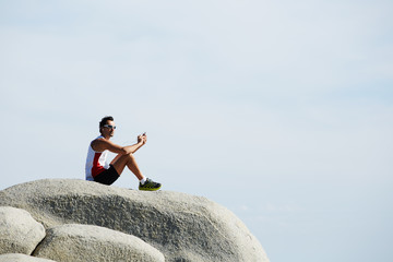 Man taking a break and relax sitting on mountain rock on sky