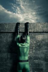 Superhero climbing a wall