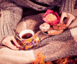 canvas print picture - hot tea and cookies in woman hands at fall season on plaid
