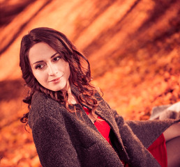 pretty brunet in coat at fall forest