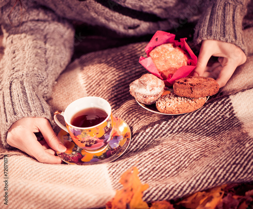 canvas print picture hot tea and cookies in woman hands at fall season on plaid