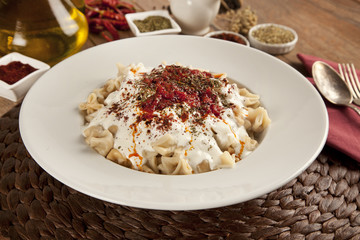 Turkish Manti manlama on plate with tomatoes sauce, yogurt