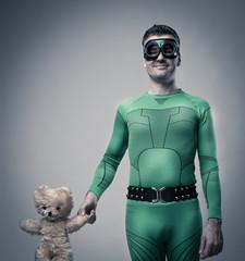 Green superhero holding a teddy bear