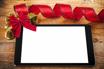 Tablet pc with christmas decorations on wooden background
