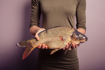 Young woman holding a carp