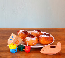 Homemade donuts and wooden dreidels (spinning top) for hanukkah
