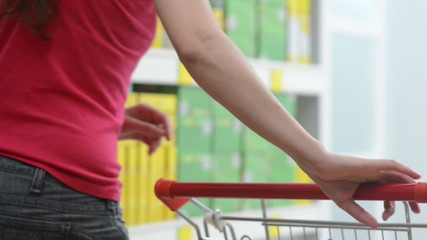Young woman taking products from store shelves at supermarket.