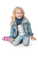 Girl in denim suit and a scarf around her neck sits putting her