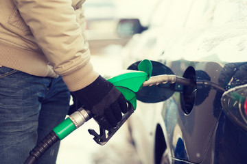 close up of male refilling car fuel tank