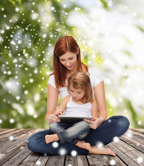 happy mother with little girl and tablet pc