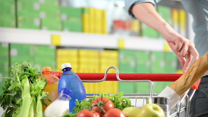 Woman walking fingers on shopping cart handle at supermarket.