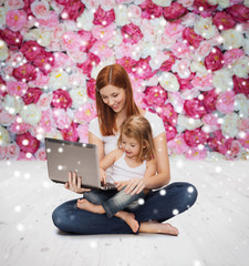 happy mother with little girl and laptop