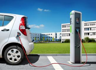Elektroauto an Stromtankstelle vor Bürogebäude Elektromobilität